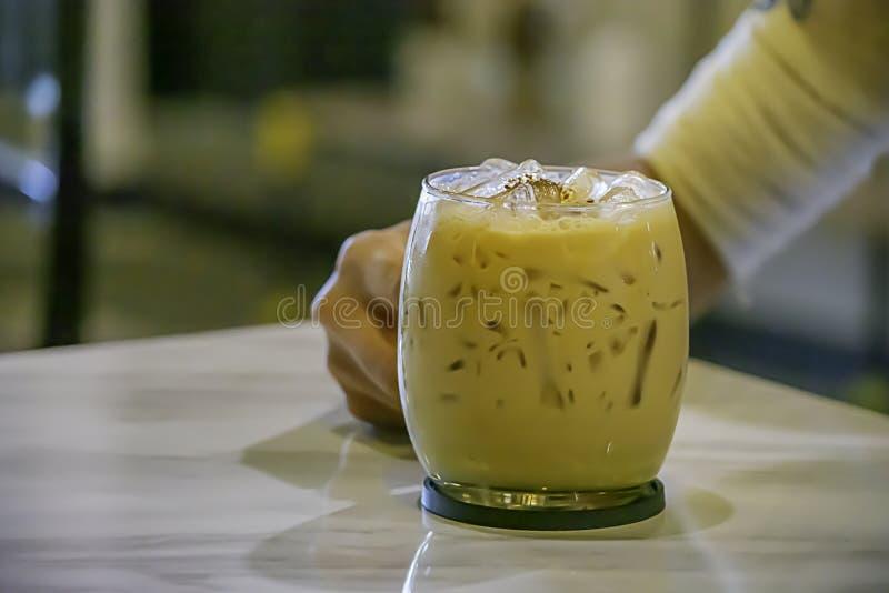 Рука держа кофе со льдом в стекле на таблице стоковые фото