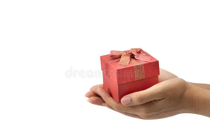 Рука держа красную подарочную коробку, используемую на Новогодняя ночь, рождество, день рождения, день Валентайн белизна изолиров стоковое фото