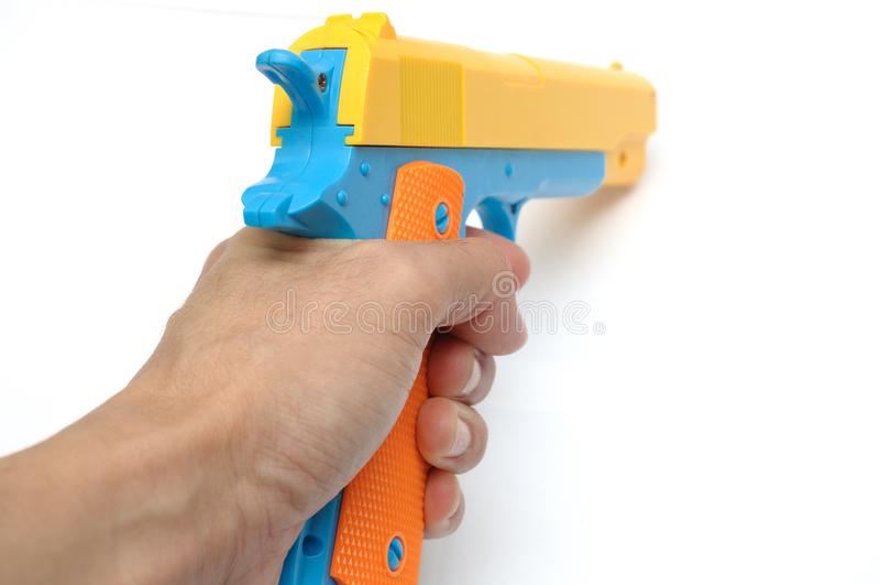 Рука держа красочное оружие руки пистолета игрушки стоковые фото