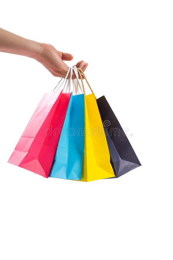 Рука держа красочные бумажные хозяйственные сумки стоковая фотография rf