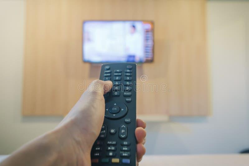 Рука держа кровать ob телевидения дистанционного управления в конце спальни вверх стоковая фотография