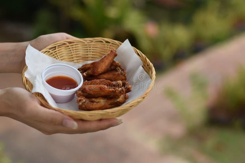 Рука держа крылья жареной курицы с погружениями в корзине стоковые фото
