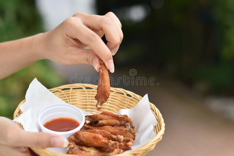 Рука держа крылья жареной курицы с погружениями в корзине стоковая фотография