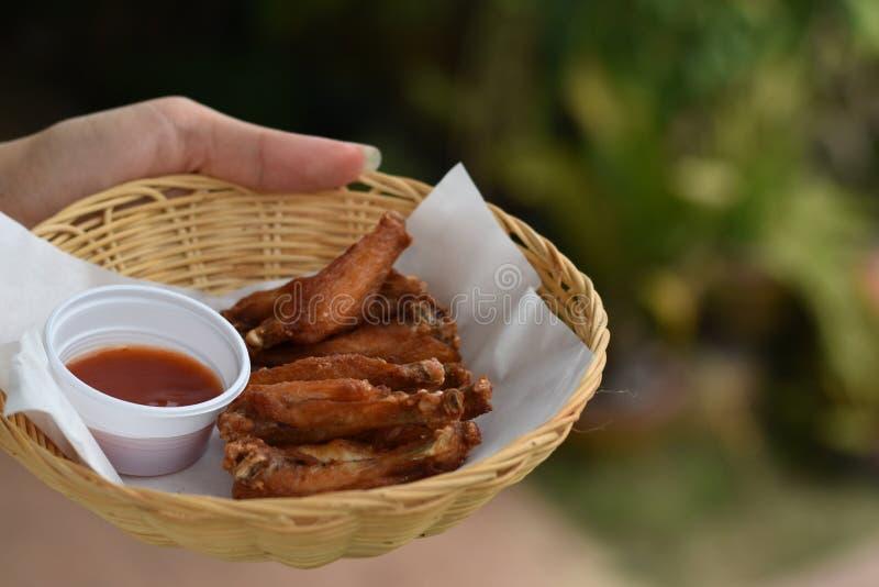 Рука держа крылья жареной курицы с погружениями в корзине стоковые изображения