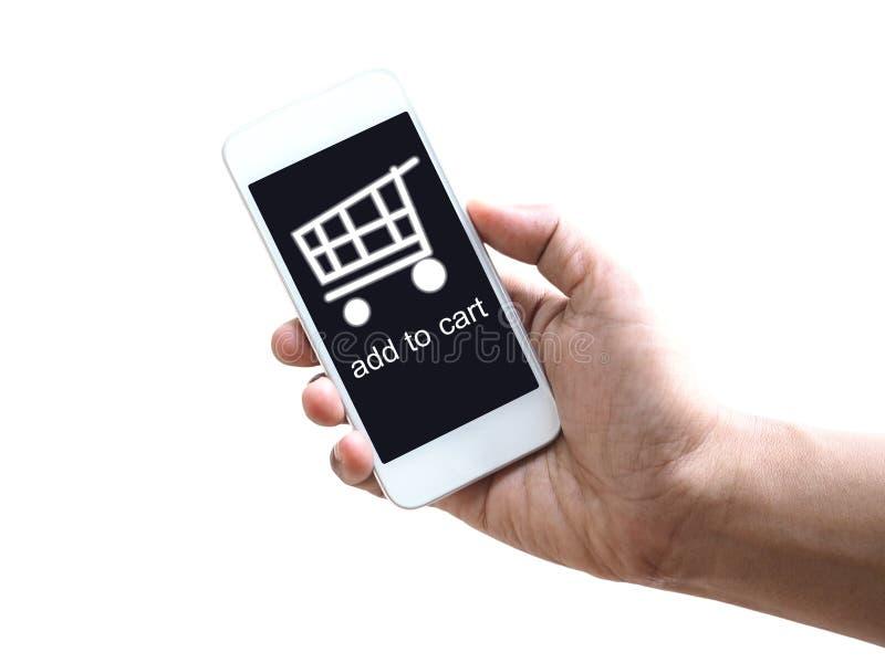 Рука держа мобильный телефон с символом тележки стоковые изображения