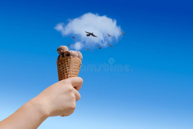 рука держа мороженое шоколада с белым облаком как летание сливочника и птицы как гарнируйте на голубом небе и белом облаке стоковые изображения rf