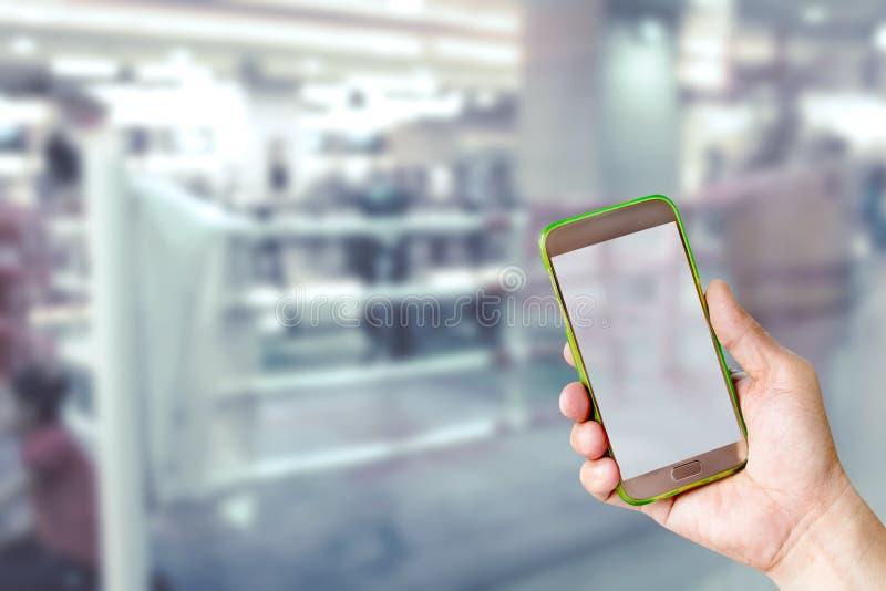 Рука держа передвижной умный телефон с предпосылкой нерезкости боксерского ринга стоковые фотографии rf