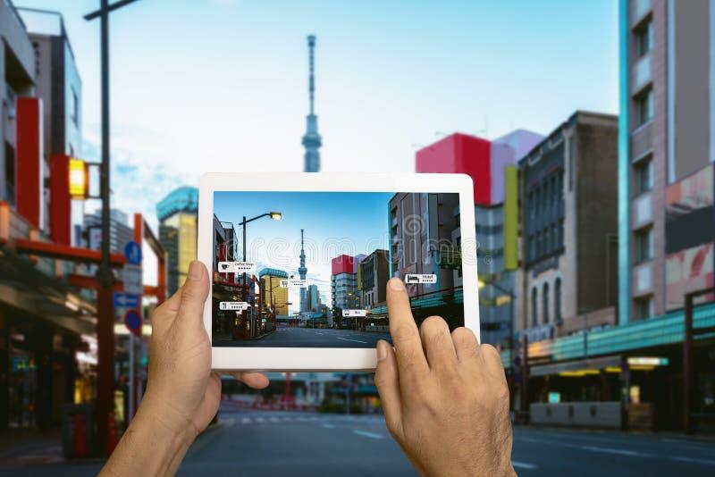 Рука держа применение AR пользы таблетки проверить релевантную информацию Город Японии в улице маркетинга стоковые фотографии rf