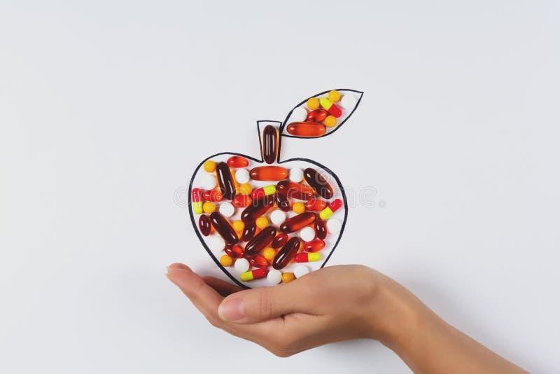 Рука держа рисуя яблоко с красочными капсулами и таблетками на белой предпосылке Витамины здравоохранения или синтетическая конце стоковое фото rf