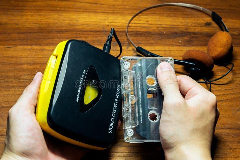Рука держа старомодных портативных игрока и кассеты кассеты стоковая фотография