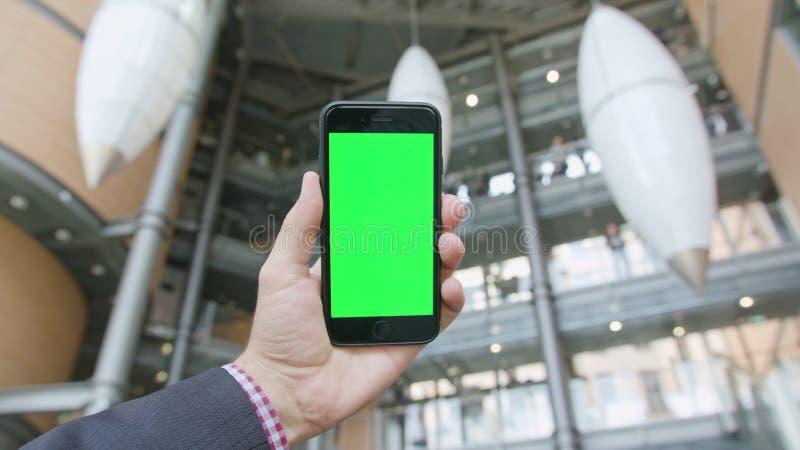Рука держа телефон с зеленым экраном стоковое фото rf
