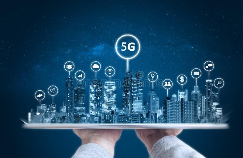 Рука держа цифровой планшет с современными значками hologram и технологии зданий Умное technolog города, 5g, интернета и сети стоковые изображения