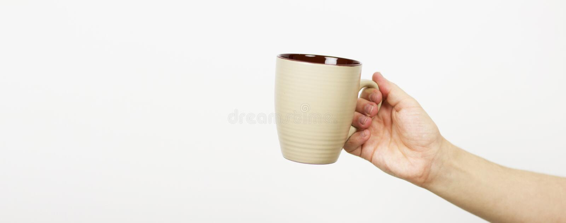 Рука держа чашку Рука держа чай, кофейную чашку, руку молодой держа серой насмешки чашки вверх E стоковое изображение