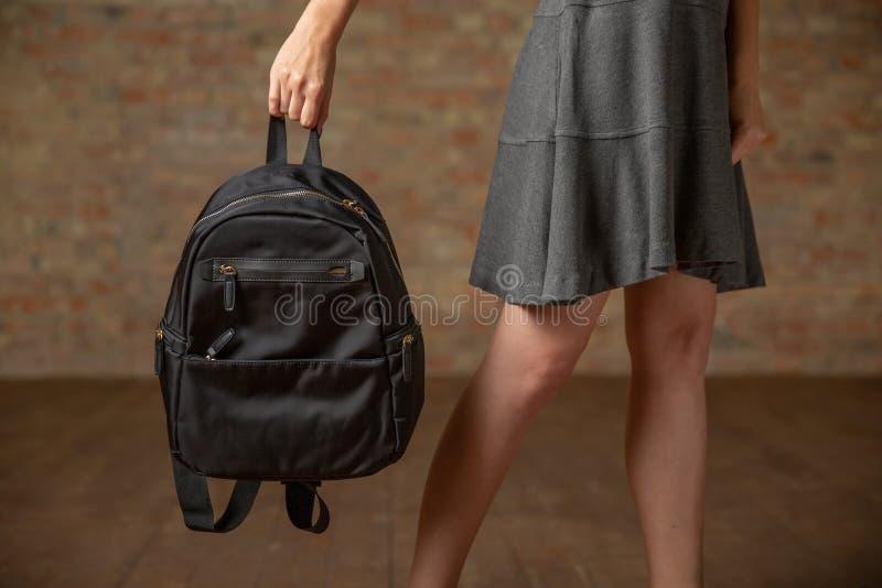 Рука держа черный рюкзак женщина состава способа стороны принципиальной схемы красотки голубая яркая стоковое изображение