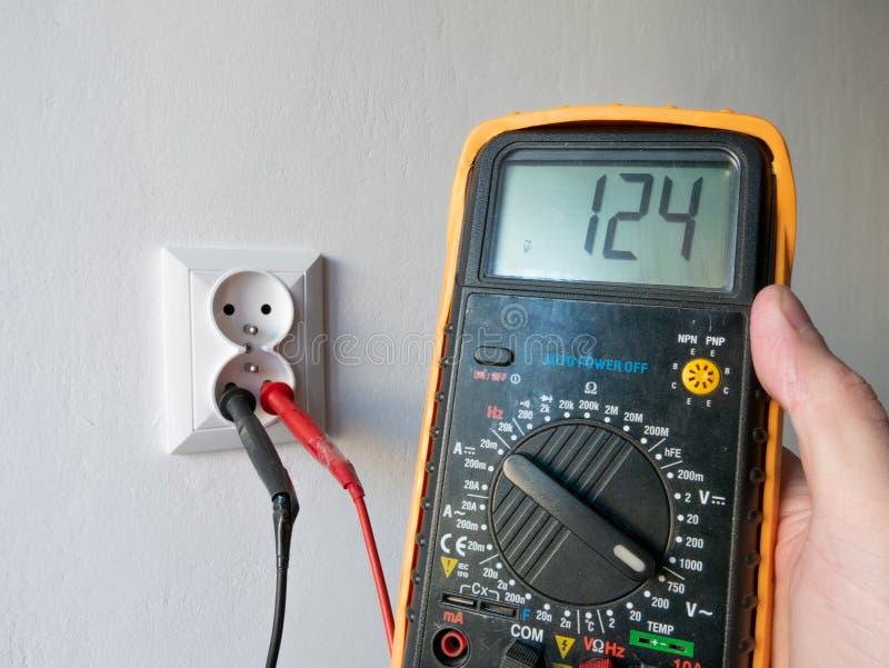 Рука держа электрический вольтамперомметр перед электрическим гнездом стоковая фотография rf