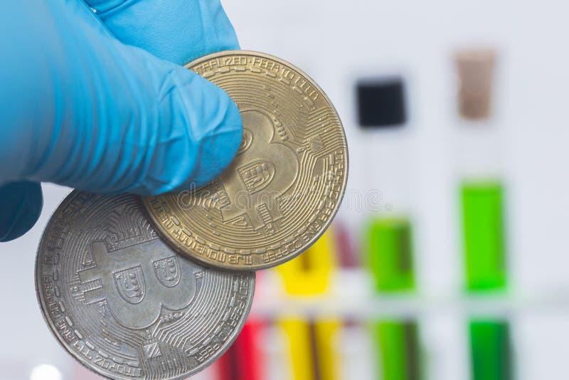 Рука держа bitcoin с жидкостью в трубке стоковая фотография