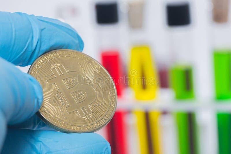 Рука держа bitcoin с жидкостью в трубке стоковое изображение