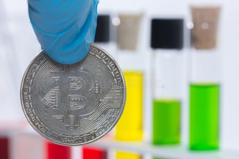 Рука держа bitcoin с жидкостью стоковая фотография rf