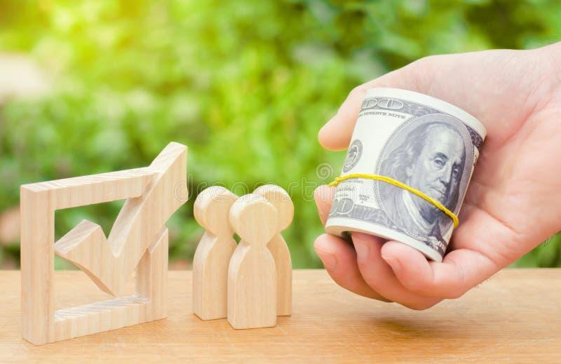 Рука держит вне деньги к людям стоя около флажка Концепция голосования и демократических выборов Коррупция и взятка стоковое изображение rf