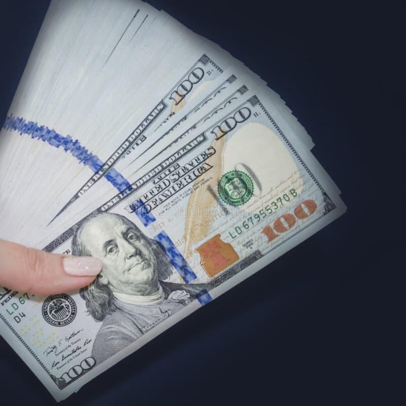 Рука держит доллары на темно-синей квадратной предпосылке стоковое изображение