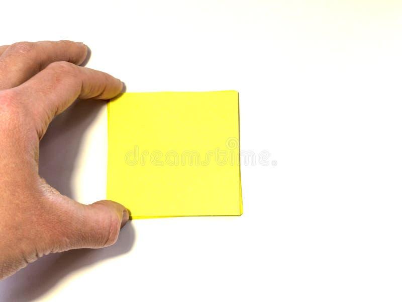 Рука держит или протягивает к желтому листу в форме квадрат бумаги в стоковые фотографии rf