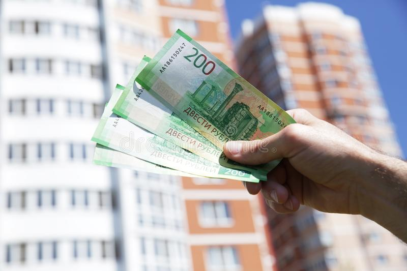 Рука держит новую русскую банкноту 200 рублей на предпосылке большого здания и голубого неба Деньги бумаги наличных денег стоковая фотография
