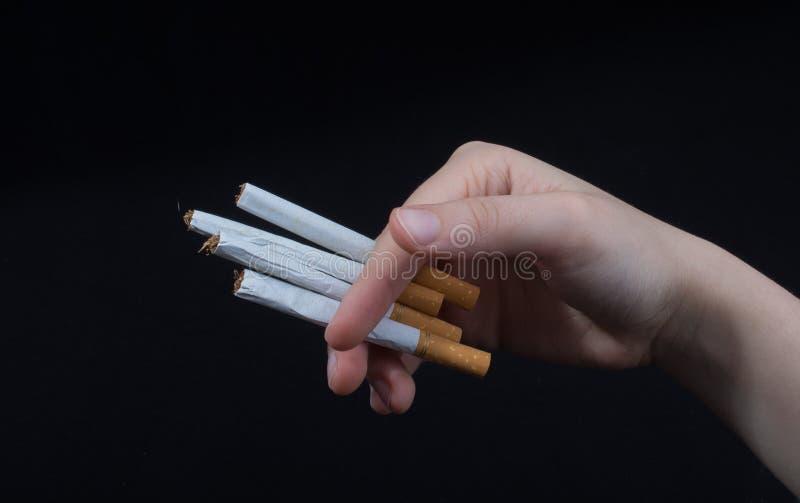Рука держит сигареты на черной предпосылке стоковое фото