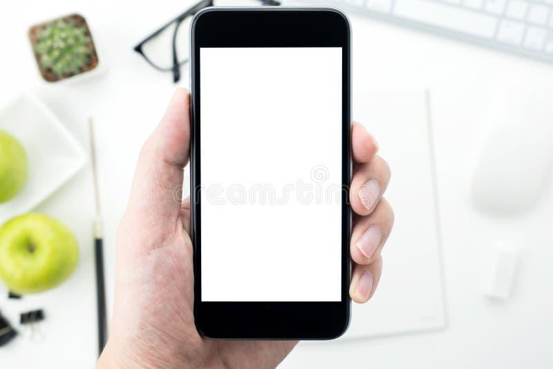Рука держит смартфон с пустым экраном модель-макета над белой таблицей стола стоковые фото