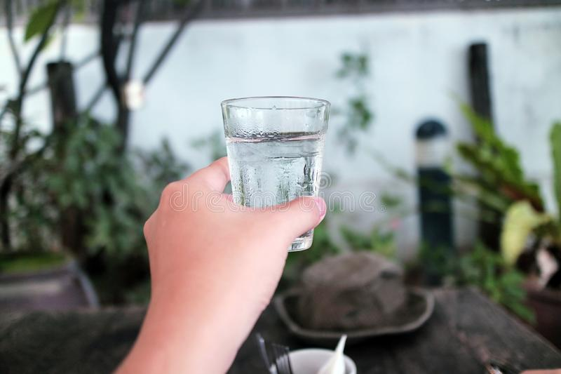 Рука держит стекло воды стоковое фото