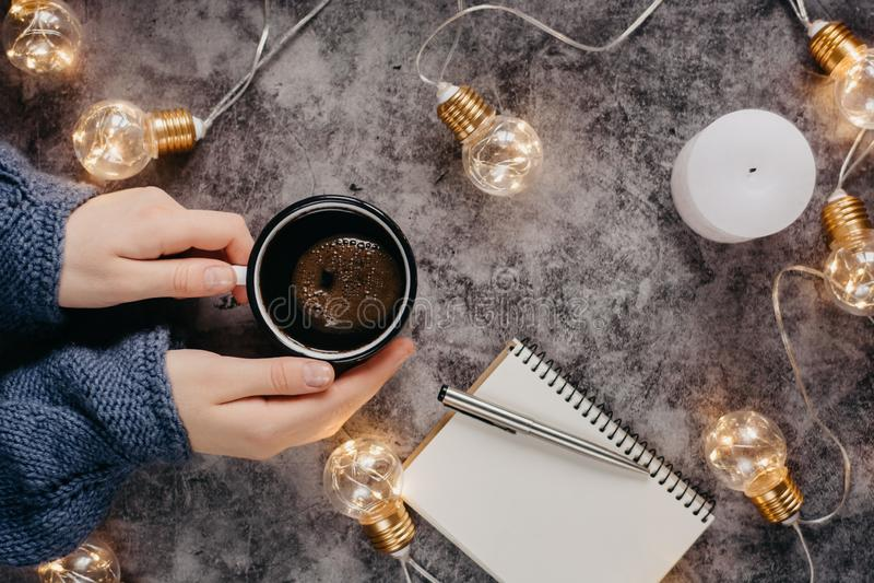 Рука держит чашку кофе на серой таблице с тетрадью, ручкой и свечой украшенными со светами приведенными стоковое фото rf
