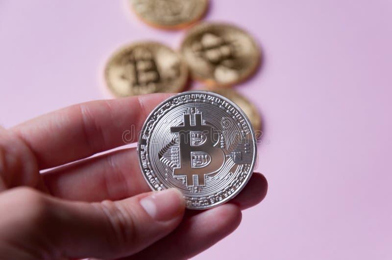 Рука держит bitcoin серебряной монеты на pinkbackground На заднем плане bitcoin нескольких золотых монеток стоковое фото