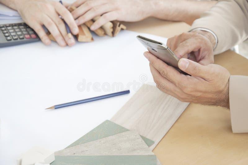 Рука дизайнера по интерьеру работая с мобильным телефоном стоковые изображения