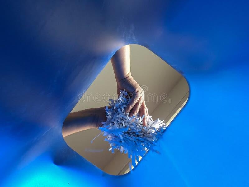Рука добавляет shredded бумагу к повторно используя ящику стоковое фото