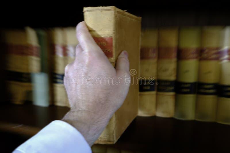 Рука достигая для книги вытягивая с полки стоковая фотография