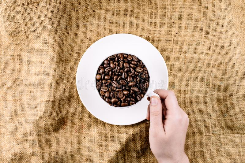 Рука достигая для кружки заполненной с кофейными зернами стоковые фотографии rf