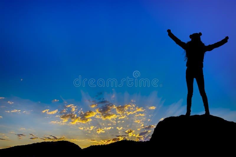 Рука достижений силуэта успешная вверх по девушке na górze холма празднуя успех с заходом солнца стоковое изображение