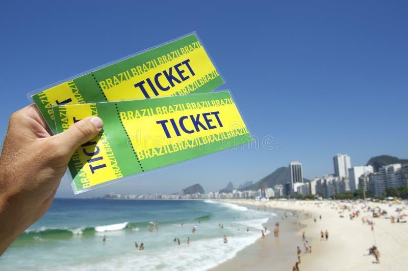 Рука держа билеты Бразилии на пляже Рио Бразилии Copacabana стоковое фото rf