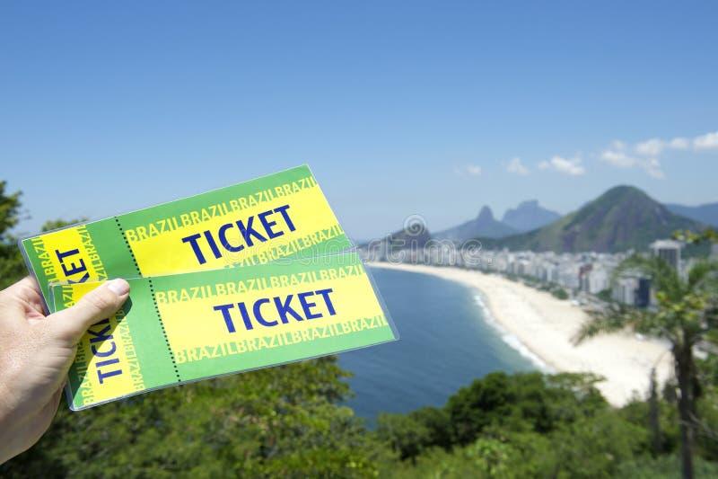 Рука держа выпускные экзамены Бразилии снабжает пляж билетами Рио стоковое фото rf