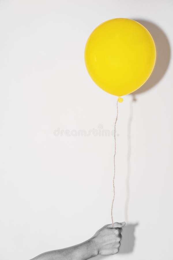 Рука держа желтый воздушный шар на белой стене стоковое фото rf