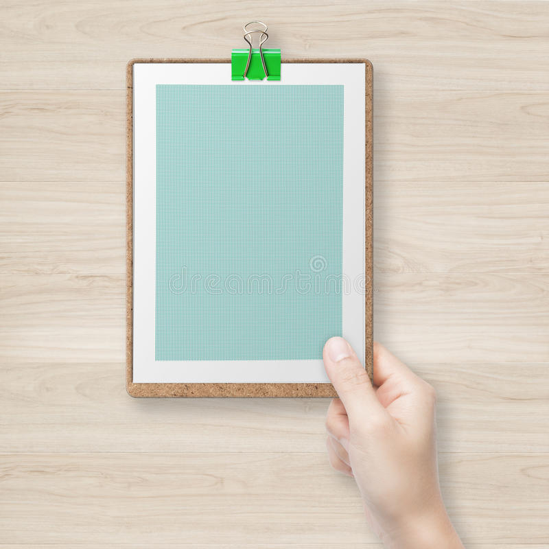 Рука держа зеленую доску сзажимом для бумаги стоковое изображение rf