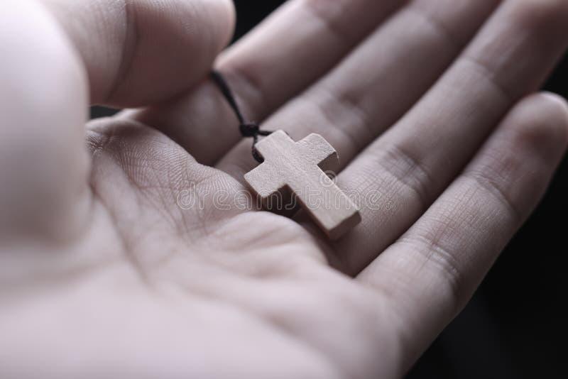 Рука держа крест стоковое фото