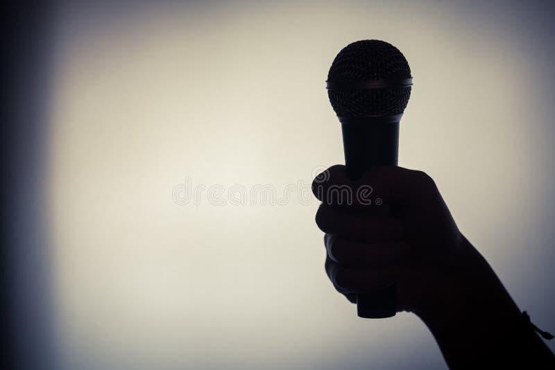 Рука держа микрофон стоковое фото