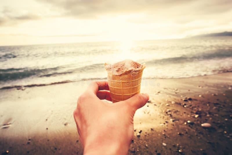 Рука держа мороженое с заходом солнца пляжа моря стоковое фото rf