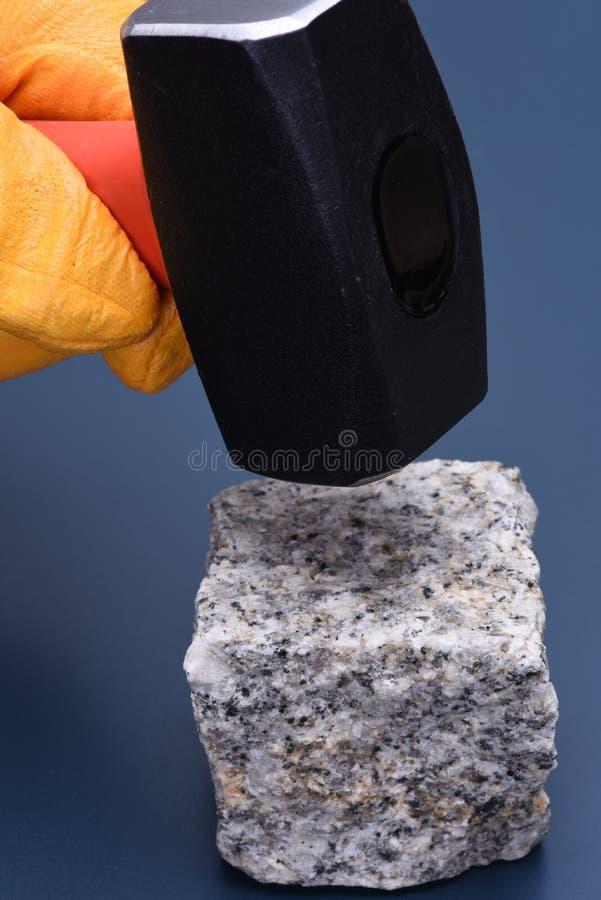 Рука держа молоток и блок камня стоковые фото