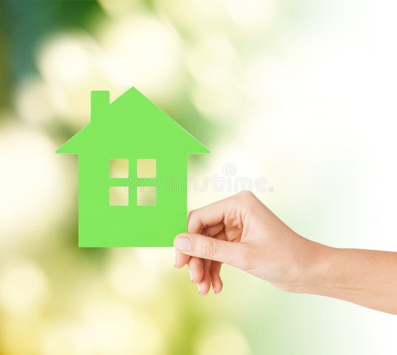 Рука держа дом зеленой книги стоковые фото