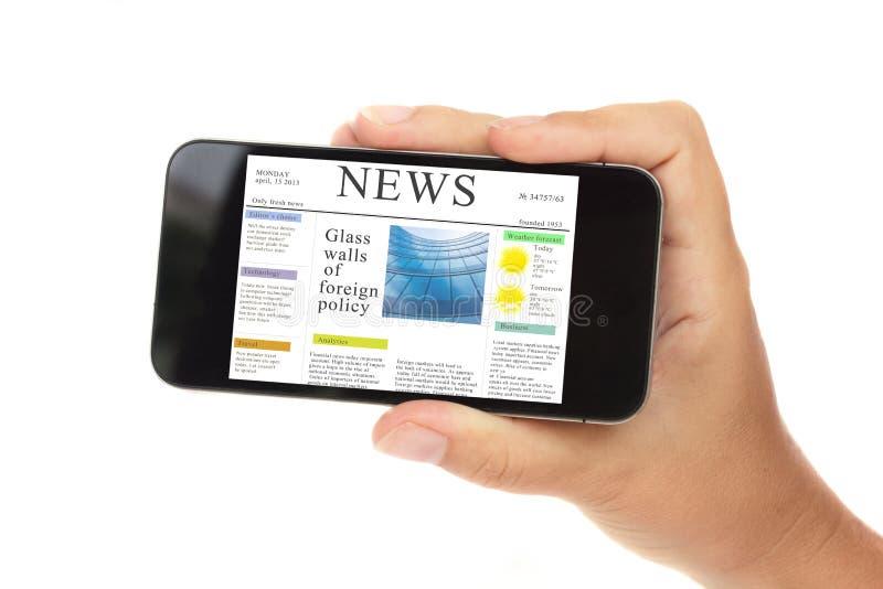 Рука держа самомоднейший телефон с новостями стоковое фото