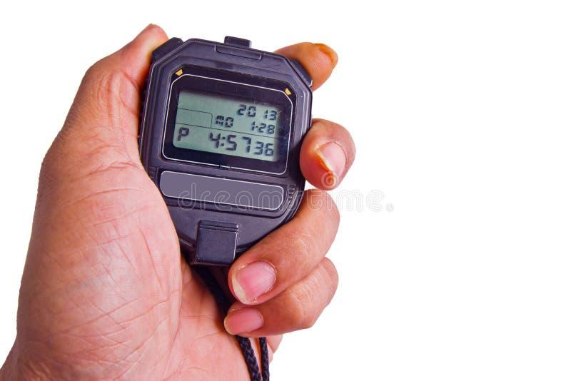 Рука держа секундомер против абстрактной предпосылки стоковое изображение rf