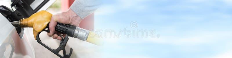 Рука держа сопло насоса для подачи топлива и refilling автомобиль стоковое фото rf