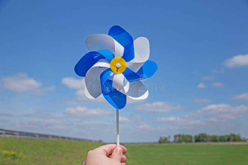 Рука держа pinwheel над горизонтом стоковые изображения