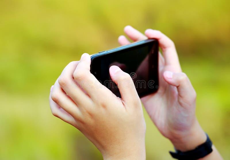 Рука держа smartphone и зеленую предпосылку природы стоковая фотография rf